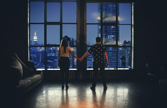 Muž a žena stoja pred veľkými oknami a držia sa za ruky