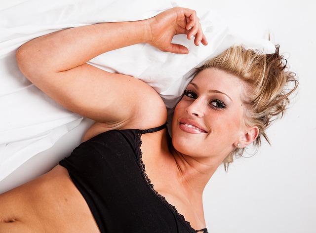 Žena s blond vlasmi v čiernej podprsenke leží na posteli.jpg