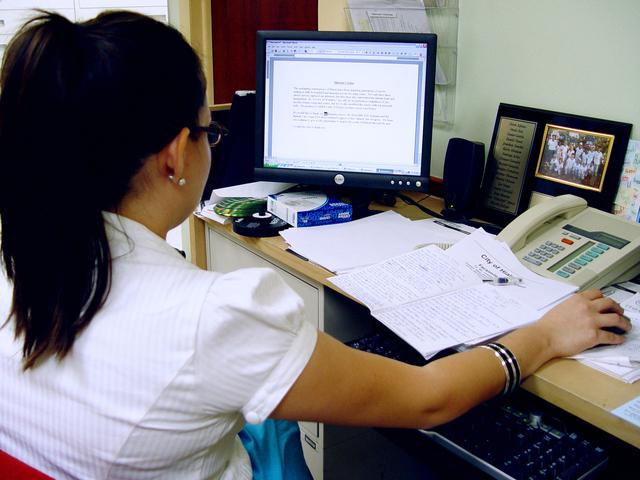 Žena pracuje s počítačom, kancelária